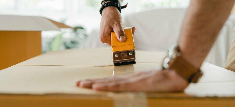 Person taping a box shut
