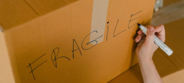 """Person writing """"fragile"""" on a box"""