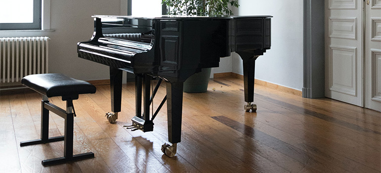 A black concert piano in a white room