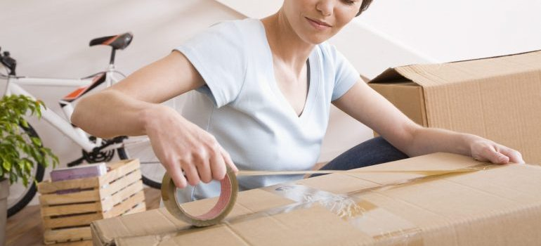 Woman taping a box closed.