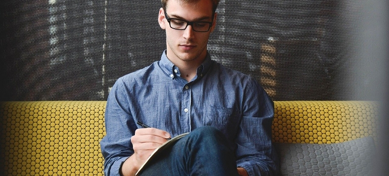 A young man sitting and writing