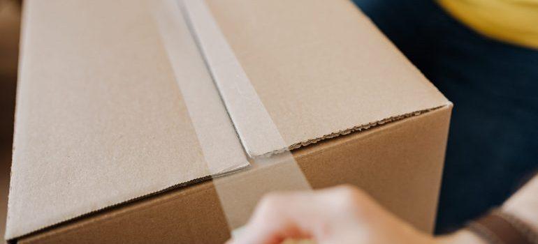 man sealing cardboard box with tape
