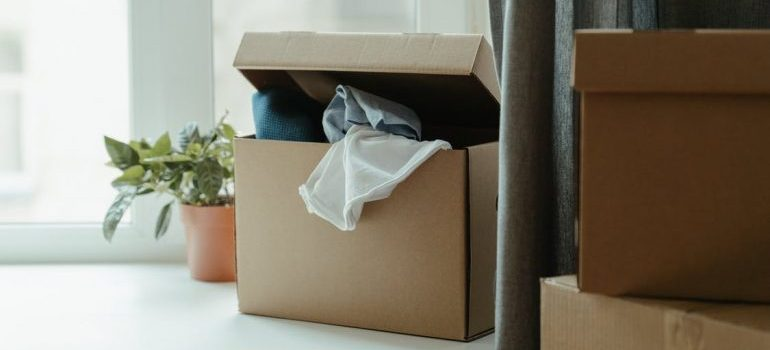 messy cardboard box with clothes
