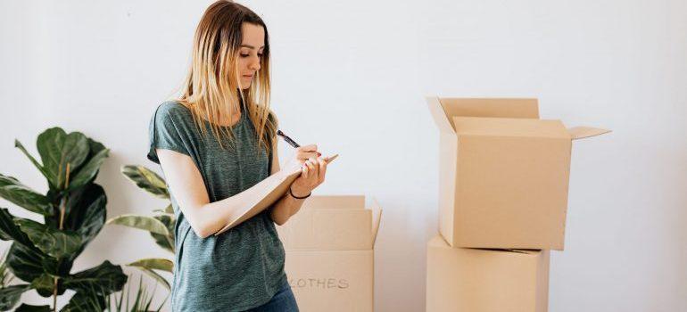 A woman writing a packing checklist