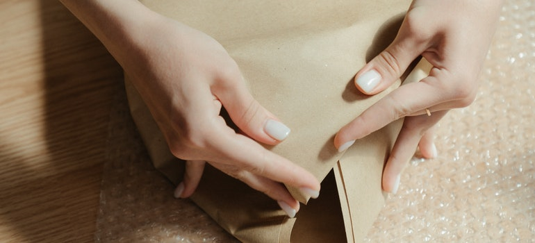 A personis packing something into wrapping paper.