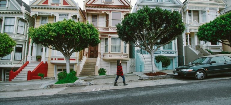 Woman in the red coat is walking on the pedestrian walk, in front of the houses and trees.