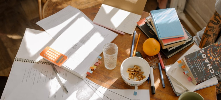 A wooden table filled with notebooks and papers